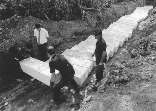 장례 노동자들이 폭염으로 사망한 무연고인의 시신을 공동묘지에 한꺼번에 묻고 있다.  글항아리 제공