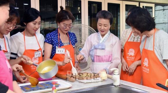 '한국의 다과상'을 수강하는 교사들이 윤숙자 한국전통음식연구소장으로부터 고구마강정의 요리 팁을 전달받고 있다.