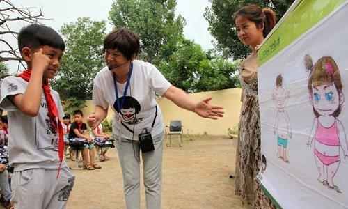 소녀 보호 기금의 한 자원봉사자가 허난성의 농촌 지역 학교에서 성폭력으로부터 자신을 보호하는 방법을 그림을 통해 설명하고 있다. 글로벌타임스 홈페이지 캡쳐