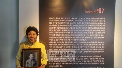지난 15일 '여순항쟁 기록전'이 열린 전남 여수 노마드갤러리에서 여순사건으로 아버지와 시아버지를 잃은 장경자씨가 아버지의 사진을 들고 서 있다.
