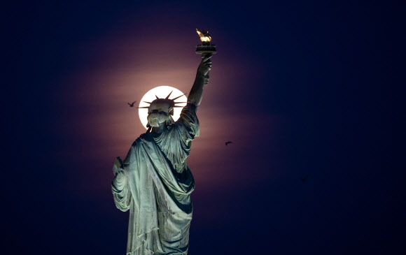 "<yonhap photo-1261=""""> (FILES) In</yonhap> (FILES) In this file photo taken on May 18, 2019 the full moon rises behind the Statue of Liberty in New York City. - Acting US immigration chief Ken Cuccinelli came under fire August 13, 2019, for twisting the words of a famed poem that appears on a plaque at the Statue of Liberty. ""Give me your tired and your poor who can stand on their own two feet and who will not become a public charge,"" Cuccinelli said on National Public Radio when asked if Emma Lazarus' ""The New Colossus"" is ""part of the American ethos."" (Photo by Johannes EISELE / AFP)/2019-08-14 09:58:27/ <연합뉴스"