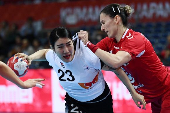 한국여자핸드볼 대표팀의 이미경(왼쪽)이 8일 일본 구마모토에서 열린 세계여자핸드볼선수권 결선리그 1그룹 첫 경기에서 세르비아 선수의 육탄 방어를 뚫고 슛을 시도하고 있다. 한국은 이날 33-36으로 져 1그룹 4위로 떨어졌다. 구마모토 AFP 연합뉴스