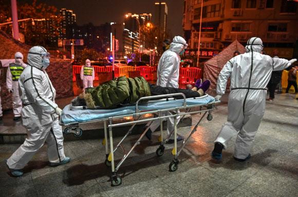 중국 급성 폐렴 발원지인 우한에서 의료진이 환자를 옮기고 있다. AFP통신 연합뉴스