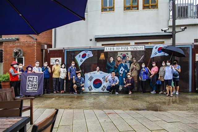 장마 중에 진행된 광복절 기념 미래유산투어를 기념하기 위해 돈의문박물관마을 '3·1운동 101주년 기념벽'에서 단체 사진을 찍고 있다.