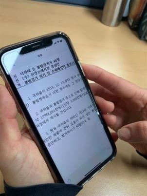 신영프레시전의 한 노동자가 26일 사측이 보낸 손해배상액 통보 메시지를 보고 있다. 신영프레시전 노조 제공