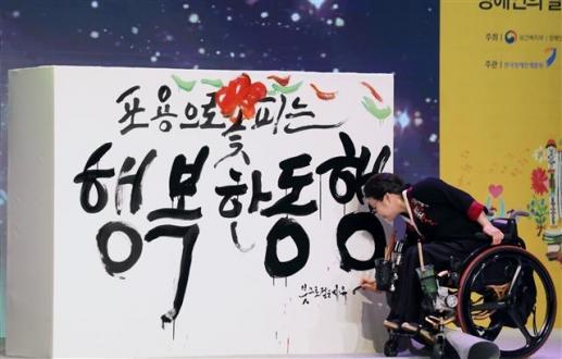 18일 서울 영등포구 여의도 63빌딩에서 열린 '제39회 장애인의 날 기념식'에서 캘리그라피 작가 이은희씨가 붓으로 '포용으로 꽃피는 행복한 동행'이라는 문구를 쓰는 기념공연을 하고 있다. 뉴스1