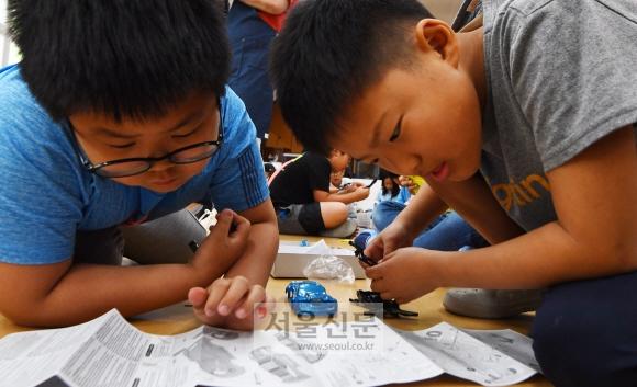 학생들이 삼삼오오 모여 앉아 서로 상의하며 미니카를 조립하고 있다.