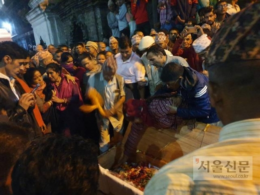 Bandana Timalsina reaches out to touch her husband's face for the last time before his cremation at the Bagmati River. Kedar Timalsina committed suicide while working at a seafood factory in Busan, July 2019. The coffin carrying his dead body arrived at the Tribhuvan International Airport in Kathmandu on August 26.