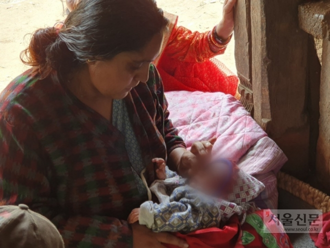 Bandana Timalsina gazes at her son at their home in Dong Kharka, Nepal, September 2, 2019. The newborn is left fatherless as his once overjoyed father Kedar Timalsina took his own life while working at a factory in South Korea.  [Ki Mindo/ The Seoul Shinmun]