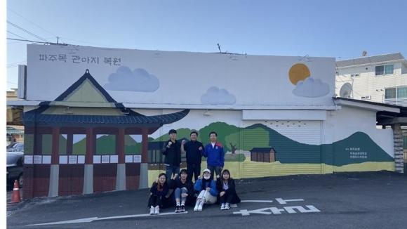 벽화 그리기 봉사활동에 참여한 두원공대 브랜드디자인학과 이종석 교수(뒷줄 오른쪽에서 첫번째)와 학생들이 완성된 벽화 앞에서 기념 촬영을 하고 있다. 두원공대 제공