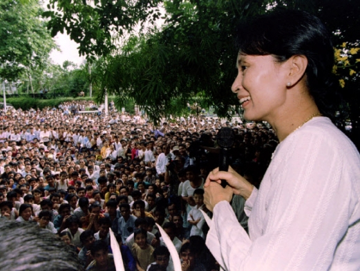 FILE PHOTO: Freed pro-democracry leader Aung San Suu Kyi smiles while speaking to hundreds of supporters from the gate at her residential compound in Yangon 1995년 아웅산 수치가 가택연금에서 풀려난 뒤 군중을 향해 연설하는 모습. 로이터 연합뉴스