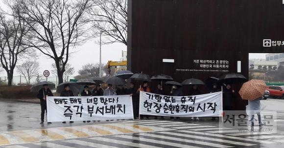 복직한 쌍용자동차 노동자들이 7일 경기 평택 쌍용차공장 안에서 해고노동자들의 부서 배치를 완료할 것을 촉구하는 현수막 시위를 하고 있다.