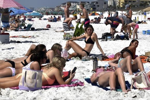 """코로나19 아랑곳 않는 미국 대학생들 코로나19 확산 방지를 위해 사회적 거리두기 권고가 내려졌지만 미국 플로리다주의 한 해변에 16일(현지시간) 대학생들이 봄방학을 맞아 몰려들어 일광욕을 즐기고 있다. 해변을 찾은 한 대학생은 """"학교보다 해변이 더 안전하다고 느낀다. 학교 기숙사에선 모두가 같은 것을 만지지 않느냐""""라고 말했다. 2020.3.17  AP 연합뉴스"""