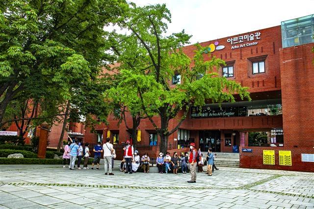 권기봉 작가가 참가자들에게 아르코예술극장 계단 앞에서 김수근과 대학로에 얽힌 이야기를 들려주고 있다.