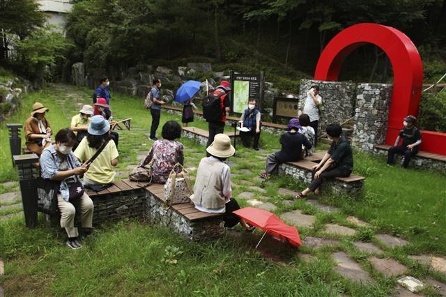 참가자들이 천왕산 성공회대 순환길 초입에 앉아 해설을 듣고 있다. 더불어 사는 삶을 강조했던 신영복 교수의 시화를 담은 36개의 팻말이 세워져 있어 사색하며 걷기 좋다.