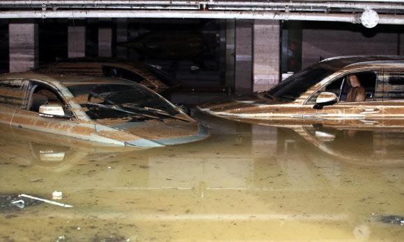 지난달 광주의 한 아파트에서 집중호우로 침수된 지하주차장의 배수 작업이 이루어지는 가운데 물에 잠긴 일부 차량이 보인다. 연합뉴스