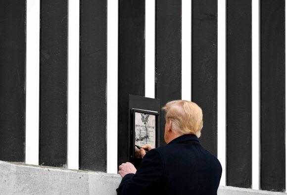 도널드 트럼프 미국 대통령이 12일(현지시간) 텍사스주 알라모의 미국·멕시코 국경장벽을 시찰하던 중 장벽에 부착된 명판에 서명을 하고 있다. 알라모 AFP 연합뉴스