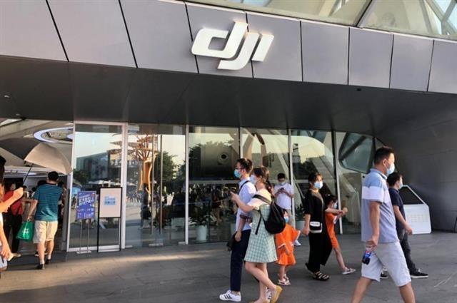 미국의 제재와 공매도 보고서 파문 등으로 세계 1위를 달리는 중국의 드론 산업이 휘청거리고 있다. 지난해 8월 중국 광둥성 선전시에서 마스크를 낀 시민들이 DJI 매장 앞을 지나는 모습. 선전 로이터 연합뉴스