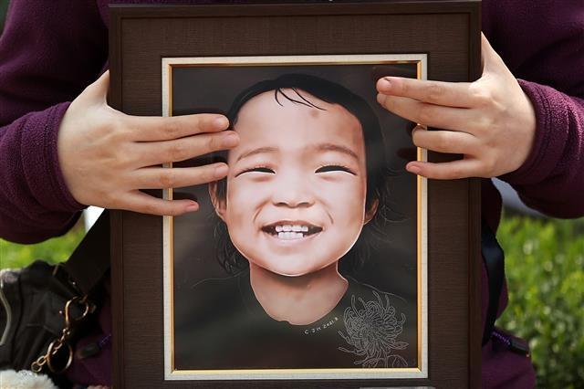 '정인이를 품에 안고' 생후 16개월 된 정인양을 입양 후 학대해 사망에 이르게 한 '양천 입양아 학대 사망' 사건에 대한 5차 공판이 열린 7일 오후 서울 양천구 남부지방법원 앞에서 시민들이 양부모에 대한 처벌을 촉구하고 있다. 2021.4.7 뉴스1