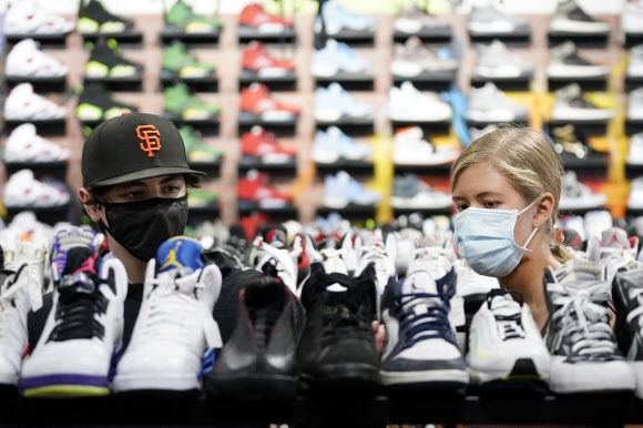 19일(현지시간) 미국 로스앤젤레스(LA)의 한 신발가게에서 고객들이 마스크를 쓴 채 쇼핑을 하고 있다. LA는 최근 코로나19 확진자 급증으로 실내 마스크 착용 의무화를 재도입했다. AP