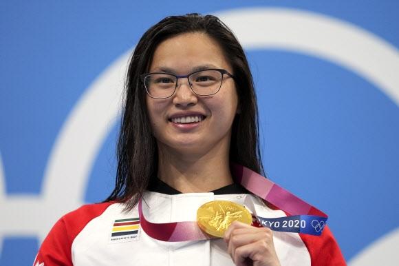 캐나다 마가렛 맥닐 선수가 26일 2020 도쿄올림픽 여자 100m 접영에서 우승한 뒤 금메달을 들어보이고 있다.  AP 연합뉴스.