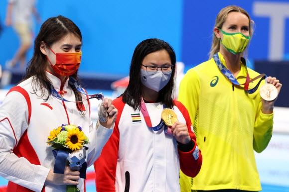 26일 2020 도쿄올림픽 여자 100m 접영 시상대에서 캐나다 마가렛 맥닐(가운데) 선수가 은메달을 딴 중국 장위페이(왼쪽) 선수와 나란히 서 있다. 로이터 연합뉴스