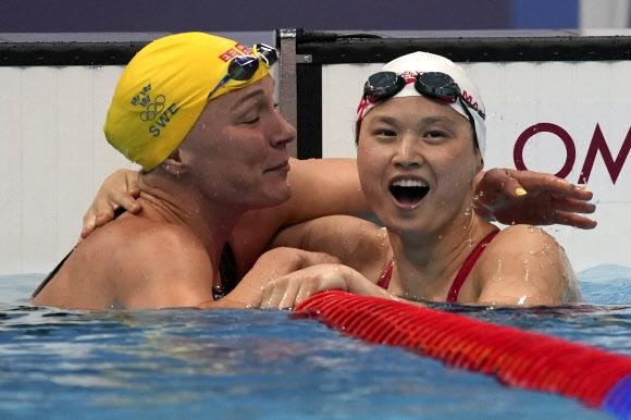 마가렛 맥닐(오른쪽) 선수가 2020 도쿄올림픽 여자 접영 100m에서 우승하자 전 세계신기록 보유자인 스웨덴의 사라 스조스트롬 선수의 축하를 받고 있다. AP 연합뉴스